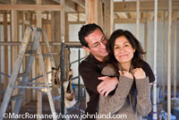 Photo of hispanic couple hugging at new construction site